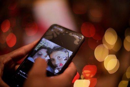 Wendolin García, quien se recuperó de COVID-19 y perdió a cuatro familiares por la enfermedad ,mira un video con fotos de su pareja fallecida en un teléfono móvil, en su casa en (Foto: Reuters)