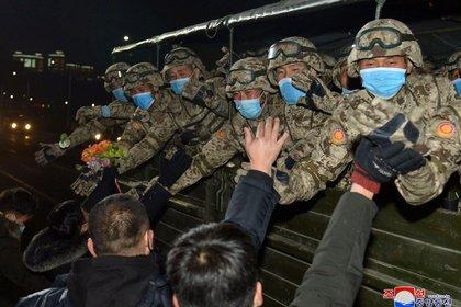 Algunos asistentes al desfile se mostraron con mascarillas para prevenir la propagación del COVID-19 (KCNA via REUTERS)