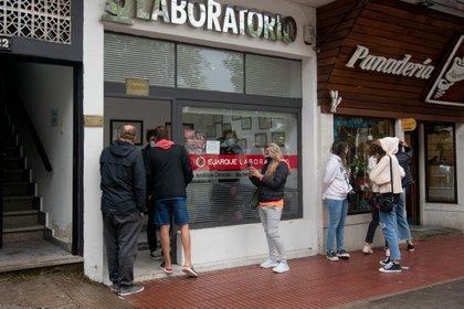Bajo la lluvia, un grupo de personas espera su turno para hisoparse en un laboratorio privado de Pinamar (Diego Medina)