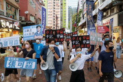 Sam Cheung Ho-sum y Wong Ji-yuet marchan en una calle para hacer campaña para las elecciones primarias destinadas a seleccionar candidatos democráticos para las elecciones de septiembre, en Hong Kong. REUTERS/Lam Yik/File Photo
