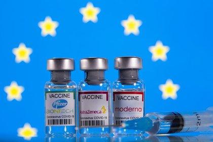 Ilustración de viales con etiquetas de vacunas anti-COVID-19 de Pfizer-BioNTech, AstraZeneca y Moderna ante una bandera de la Unión Europea (UE), 19 de marzo de 2021. REUTERS/Dado Ruvic