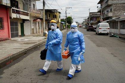 IMAGEN DE ARCHIVO. Médicos que forman parte de una unidad de rápida respuesta del Ministerio de Salud ecuatoriano caminan a una residencia para tomar muestras de personas que se sospecha tienen COVID-19, en Guayaquil, Ecuador, Abril 29, 2020. REUTERS/Santiago Arcos