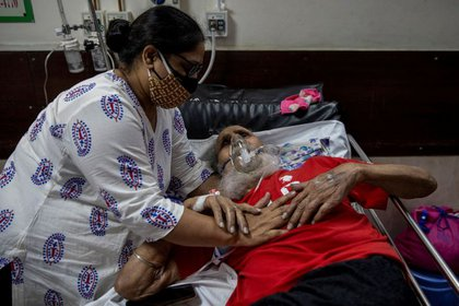 Un hombre sufriendo la enfermedad de coronavirus (COVID-19) es consolado por su hija mientras recibe tratamiento en un hospital en Nueva Delhi, India, 1 de mayo, 2021. REUTERS/Danish Siddiqui
