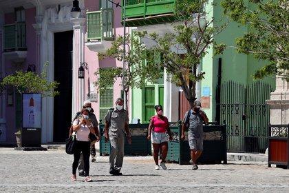Varias personas caminan el 27 de abril de 2021 con tapabocas en La Habana (Cuba). EFE/ Ernesto Mastrascusa