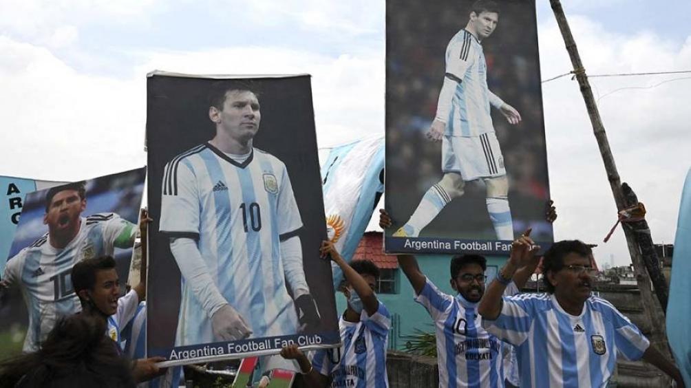 """Los hinchas levantan grandes fotografías del capitán del seleccionado con la leyenda """"Argentina Football Fans Club"""". Foto: AFP."""